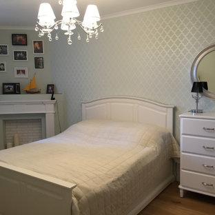 Immagine di una camera matrimoniale chic di medie dimensioni con pareti beige, pavimento in laminato, camino ad angolo, pavimento beige e carta da parati