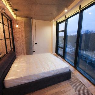 Imagen de dormitorio principal, urbano, pequeño, sin chimenea, con paredes blancas, suelo laminado y suelo beige