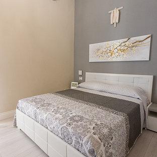 Diseño de dormitorio principal, actual, pequeño, con paredes grises, suelo laminado y suelo gris