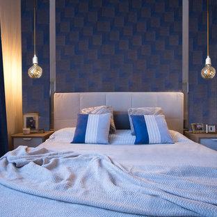 Modelo de dormitorio principal, minimalista, de tamaño medio, con paredes azules, suelo de baldosas de cerámica y suelo marrón