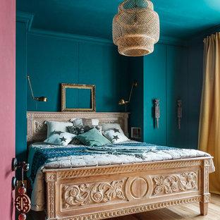 Modelo de dormitorio principal, bohemio, con paredes verdes, suelo de madera en tonos medios y suelo marrón