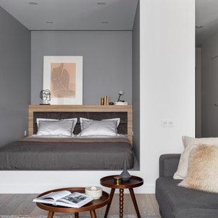 Идея дизайна: спальня в современном стиле с серыми стенами, паркетным полом среднего тона и коричневым полом
