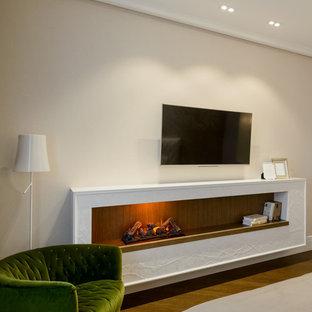 Стильный дизайн: хозяйская спальня среднего размера с бежевыми стенами, пробковым полом, подвесным камином, фасадом камина из штукатурки и коричневым полом - последний тренд
