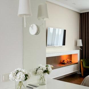 На фото: со средним бюджетом хозяйские спальни среднего размера с бежевыми стенами, пробковым полом, подвесным камином, фасадом камина из штукатурки и коричневым полом