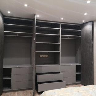 Diseño de dormitorio principal, contemporáneo, grande, sin chimenea, con paredes negras, suelo de madera en tonos medios, marco de chimenea de hormigón y suelo beige