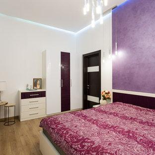 Modelo de dormitorio principal, contemporáneo, de tamaño medio, con paredes blancas, suelo laminado y suelo beige