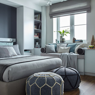 Example of a mid-sized danish medium tone wood floor bedroom design in Moscow with blue walls