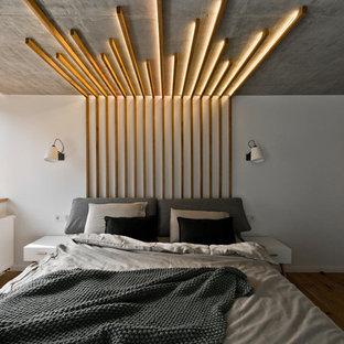 Свежая идея для дизайна: спальня в стиле лофт с белыми стенами, паркетным полом среднего тона и коричневым полом для хозяев - отличное фото интерьера