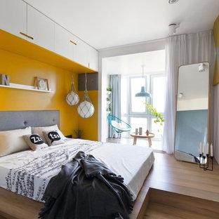 На фото: хозяйская спальня в современном стиле с желтыми стенами, паркетным полом среднего тона и коричневым полом с