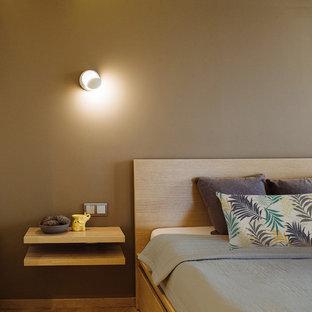 Cette image montre une petit chambre parentale minimaliste avec un mur marron, un sol en bois brun, aucune cheminée, un manteau de cheminée en brique et un sol jaune.
