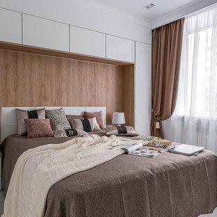 Пример оригинального дизайна: хозяйская спальня в современном стиле с белыми стенами, белым полом и правильным освещением
