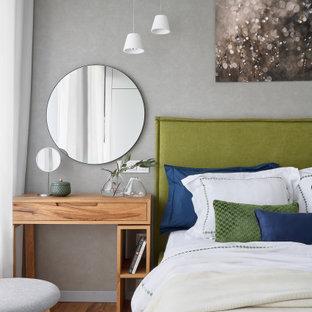 На фото: большая спальня в современном стиле с серыми стенами, паркетным полом среднего тона и коричневым полом с