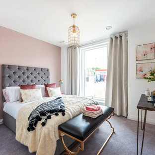This is an example of a contemporary grey and pink bedroom in London with pink walls, carpet and grey floors.