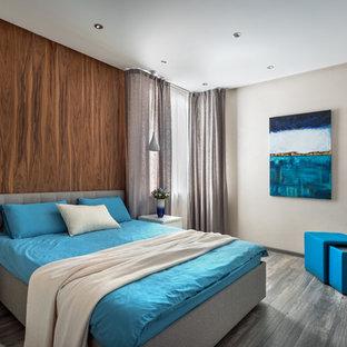 На фото: со средним бюджетом спальни среднего размера в современном стиле с полом из ламината и коричневыми стенами