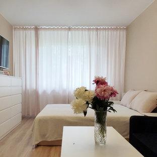 Ejemplo de dormitorio principal, actual, pequeño, sin chimenea, con paredes beige, suelo laminado y suelo marrón