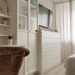 Foto de dormitorio principal, actual, pequeño, sin chimenea, con paredes beige, suelo laminado y suelo marrón