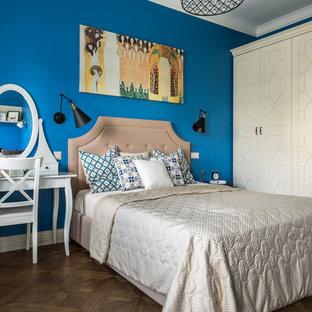 Inredning av ett klassiskt mellanstort huvudsovrum, med blå väggar, mörkt trägolv och brunt golv