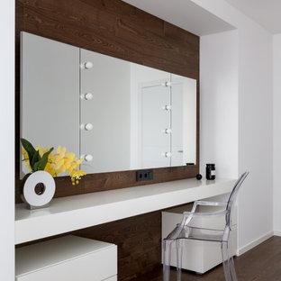 Cette image montre une chambre parentale design en bois de taille moyenne avec un mur blanc, un sol en bois brun et un sol marron.