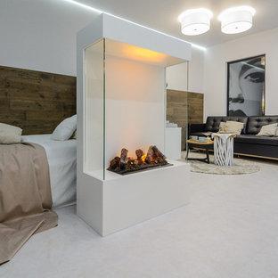 Diseño de dormitorio principal, actual, pequeño, con paredes blancas, chimenea lineal, marco de chimenea de metal y suelo blanco