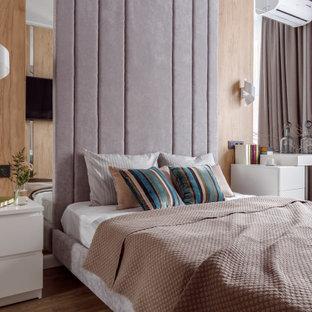 На фото: большая хозяйская спальня в современном стиле с белыми стенами, коричневым полом и рабочим местом