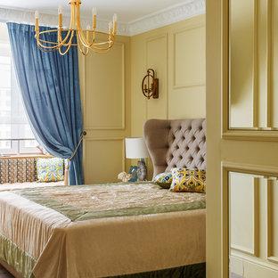 На фото: хозяйская спальня в классическом стиле с желтыми стенами, паркетным полом среднего тона и коричневым полом с