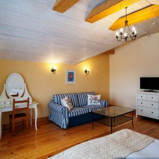 Ejemplo de habitación de invitados urbana, sin chimenea, con paredes amarillas y suelo de madera pintada
