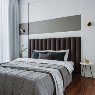 Mid-sized contemporary master bedroom in Moscow with grey walls, laminate floors and brown floor.