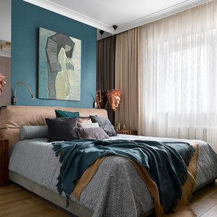 На фото: хозяйская спальня среднего размера в современном стиле с синими стенами и паркетным полом среднего тона без камина с