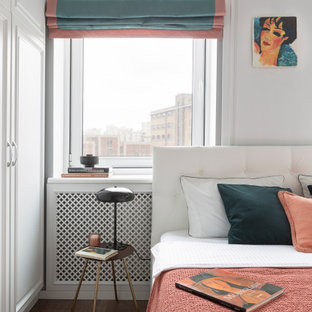 На фото: маленькая хозяйская спальня в современном стиле с белыми стенами, полом из ламината, коричневым полом и панелями на стенах