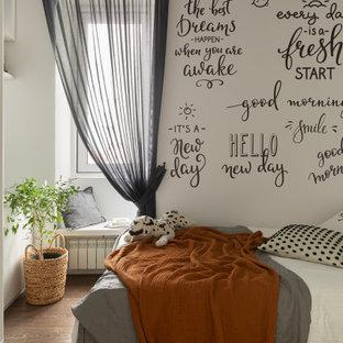 Exemple d'une petit chambre parentale tendance avec un mur blanc, sol en stratifié, un sol marron et du papier peint.