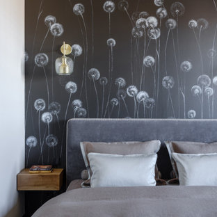 This is an example of a small contemporary master bedroom in Moscow with beige walls, laminate floors and black floors.