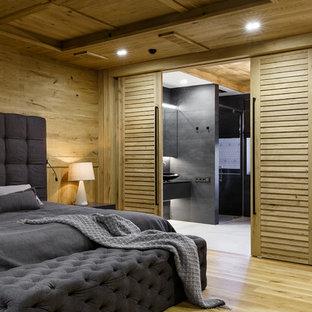 Ejemplo de dormitorio principal, industrial, con paredes marrones, suelo de madera clara y suelo beige