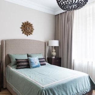 На фото: спальня в стиле современная классика с серыми стенами, паркетным полом среднего тона и коричневым полом для хозяев с