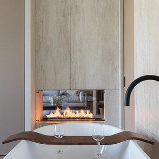 Свежая идея для дизайна: хозяйская спальня в современном стиле с темным паркетным полом, двусторонним камином, коричневым полом и фасадом камина из камня - отличное фото интерьера