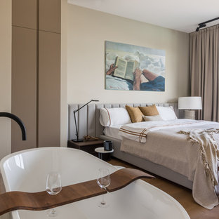 На фото: хозяйские спальни в современном стиле с темным паркетным полом и коричневым полом