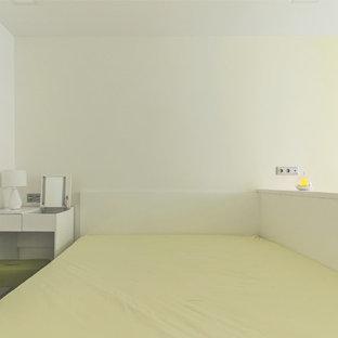 Modelo de dormitorio principal, actual, pequeño, sin chimenea, con paredes amarillas, suelo de corcho y suelo blanco