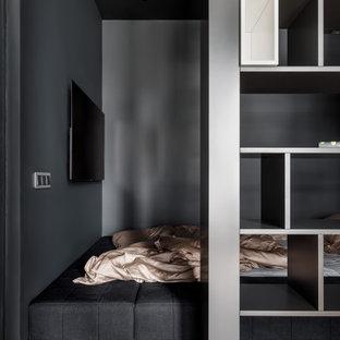 На фото: хозяйская спальня в современном стиле с черными стенами, паркетным полом среднего тона, коричневым полом и телевизором