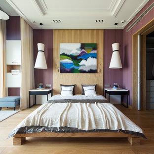 Exemple d'une chambre parentale tendance avec un mur violet et un sol en bois clair.