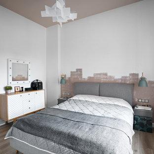 На фото: хозяйские спальни в скандинавском стиле с белыми стенами, паркетным полом среднего тона и серым полом