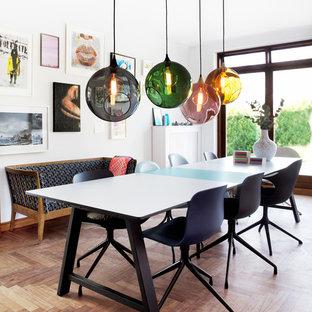 Inspiration pour une salle à manger ouverte sur le salon design de taille moyenne avec un mur blanc et un sol en bois brun.