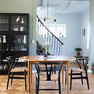 Diseño de comedor nórdico con paredes verdes y suelo de madera en tonos medios