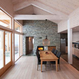 Immagine di una sala da pranzo aperta verso la cucina nordica con parquet chiaro e stufa a legna