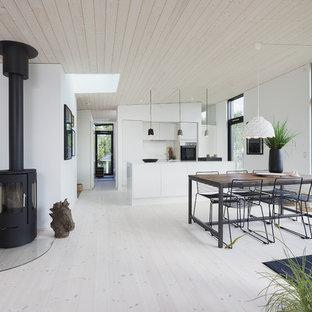 Esempio di una sala da pranzo nordica con pareti bianche, stufa a legna, cornice del camino in metallo, pavimento bianco e parquet chiaro