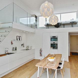 Foto di una piccola sala da pranzo aperta verso la cucina nordica con pareti bianche e parquet chiaro