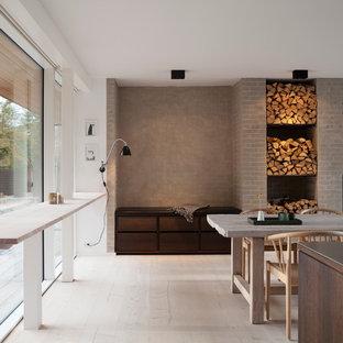 Ejemplo de comedor de cocina nórdico, grande, con paredes blancas, suelo de madera clara y chimenea lineal