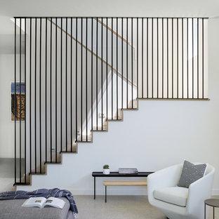 Foto de escalera en U, actual, con escalones de madera, contrahuellas de madera y barandilla de metal