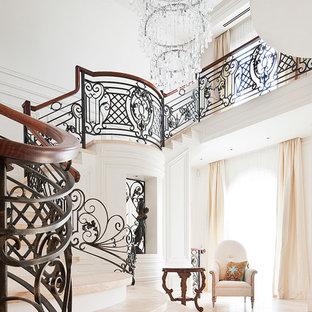 На фото: большая изогнутая лестница в классическом стиле с крашенными деревянными подступенками и ступенями из травертина с