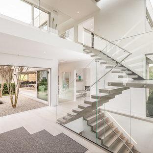 Ispirazione per un'ampia scala sospesa design con nessuna alzata e parapetto in vetro
