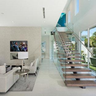 Foto de escalera recta, moderna, de tamaño medio, con contrahuellas de vidrio y barandilla de metal