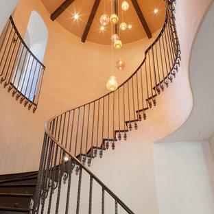 Modelo de escalera curva, mediterránea, grande, con escalones de madera, contrahuellas de madera y barandilla de metal